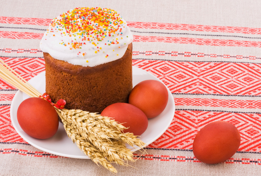 Easter Cake, Painted Eggs and Ears of Wheat on traditional tablecloth